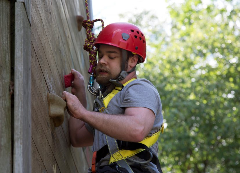 Camper climbing the climbing wall wearing helmet and harness
