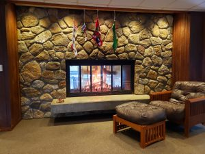 Stone fireplace with a roaring fire and stockings hanging above. An easy chair alongside the fireplace.